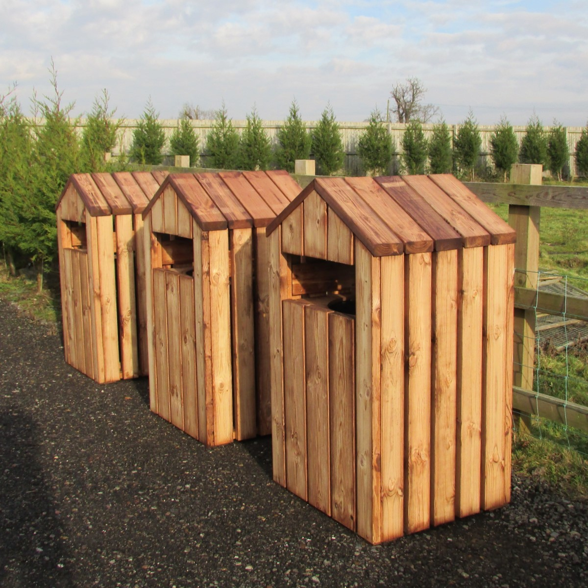 3 wooden litter bins with pitched roof lids in a line on tarmac path