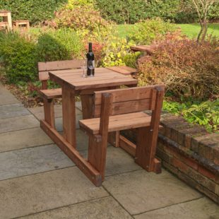 A solidly built wooden 2 seater picnic table located on a pub patio