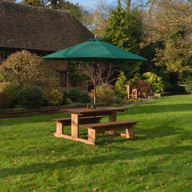 A 6 seat wooden picnic bench with rectangular table and two fixed benches