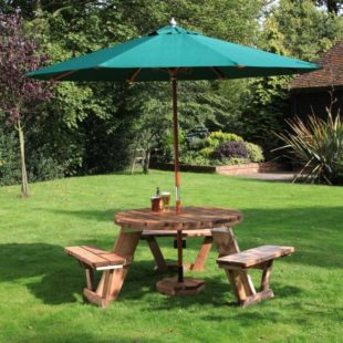 A robust circular wooden picnic table with seats for 6 people and a green parasol on a lawn
