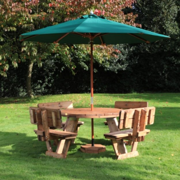 A circular picnic table with 8 seats with back rests on a lawn