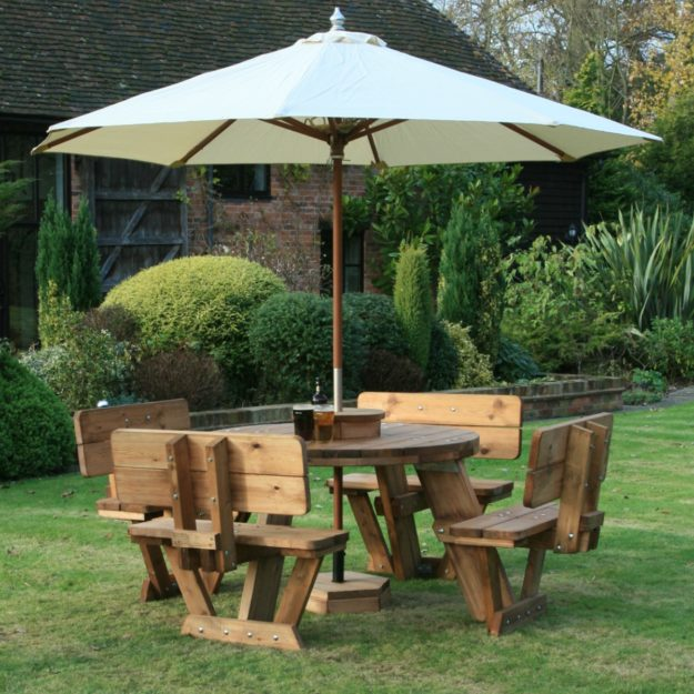 A circular wooden picnic table with backrests and a cream parasol located on a lawn