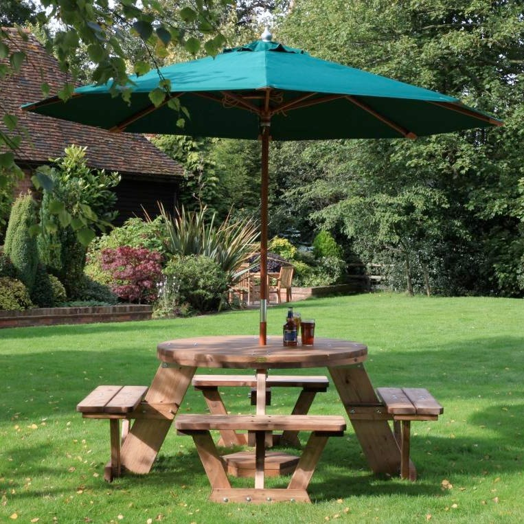 A circular wooden picnic table seating up to 8 people located on a lawn with a green parasol