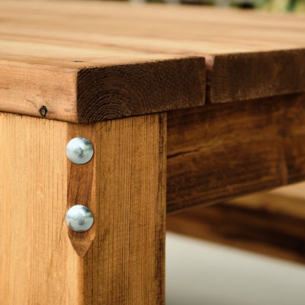 A close up of a wooden rectangular outdoor dining table corner showing very thick wood planks and a heavy duty bolt