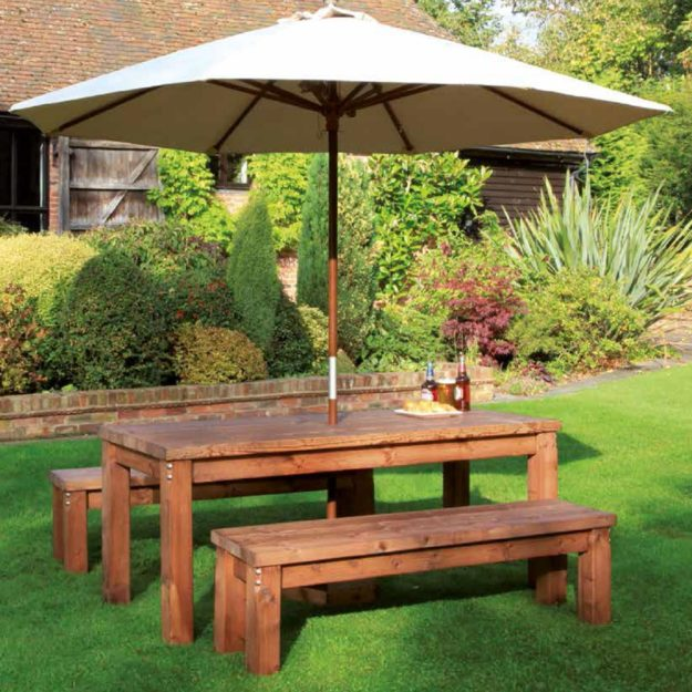 A chunky wooden rectangular table with backless wooden benches either side and a cream parasol