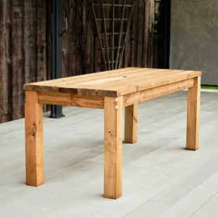 A chunky wooden rectangular outdoor dining table made from fsc certified timber on a grey deck