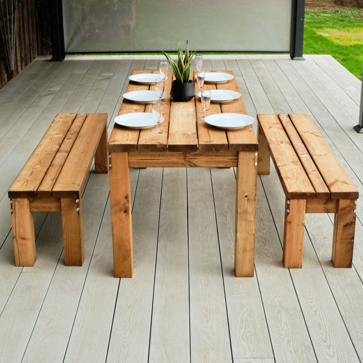 A chunky wooden rectangular outdoor dining table and 2 benches end of view on a grey deck with table set for dinner