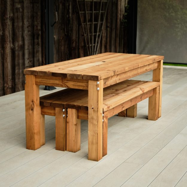 A commercial outdoor rectangular wooden dining table and bench set showing the benches stored under the table