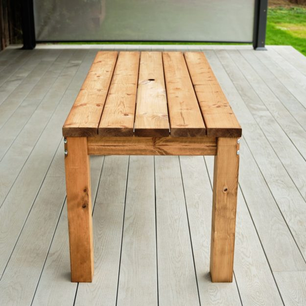 An end on view of a rectangular chunky wooden outdoor dining table on a grey deck