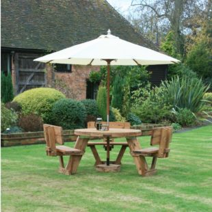 A circular wooden picnic table seating 6 people, the seats have back rests and there is a cream parasol all on a lawn