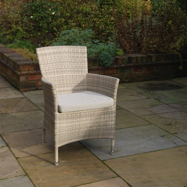 An elegant outdoor rattan armchair, cream grey weave located on a patio