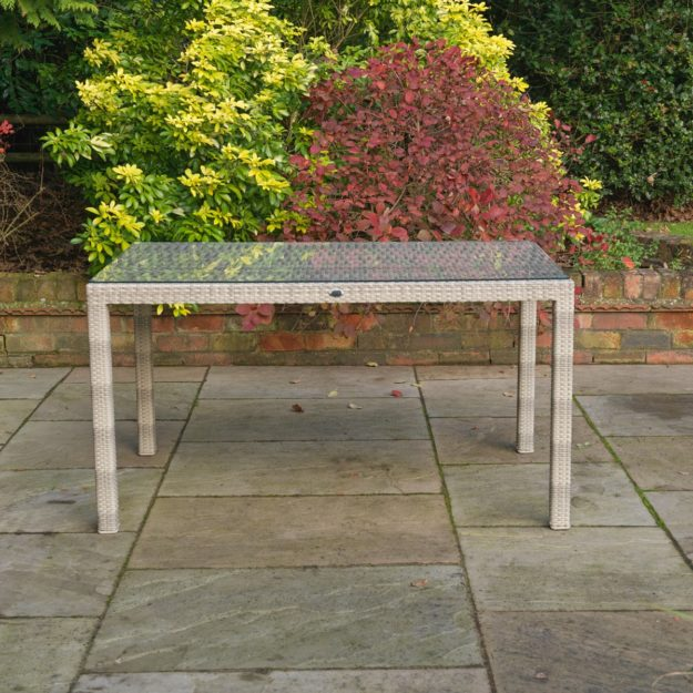 An outdoor rectangular table made from cream grey rattan with a tempered safety glass table top
