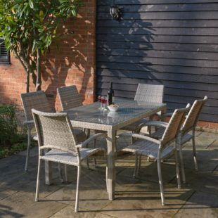 A rectangular outdoor dining table in cream grey weave rattan with 6 matching arm chairs arranged around it located on a patio