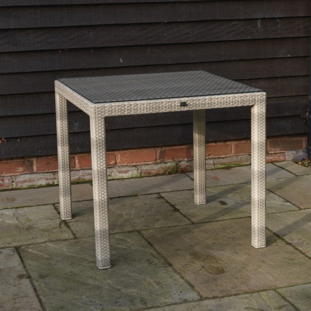 A square outdoor dining table in cream grey rattan with a tempered safety glass table top located on a patio