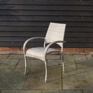 A cream grey weave rattan outdoor dining chair with arms located on a patio