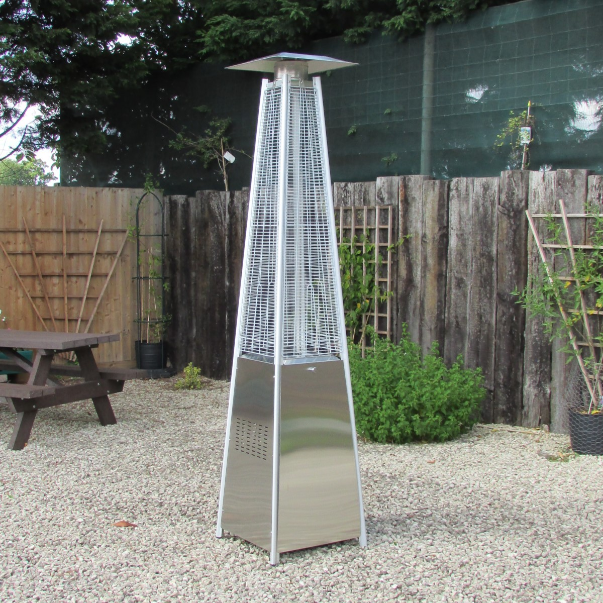 A pyramid gas patio heater located on a gravel courtyard