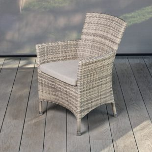 A cream grey rattan outdoor dining armchair on a grey deck