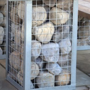 A close up of large round stones in a gabion metal cage