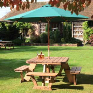 A square wooden picnic table seating 8 people with a green parasol on a lawn