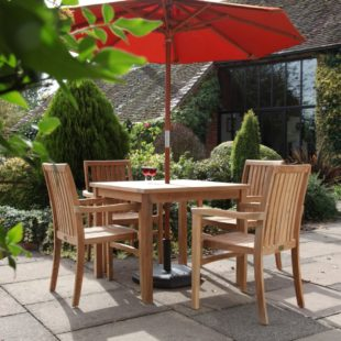 A square teak outdoor dining table with 4 armchairs around it on a patio with a terracotta coloured parasol
