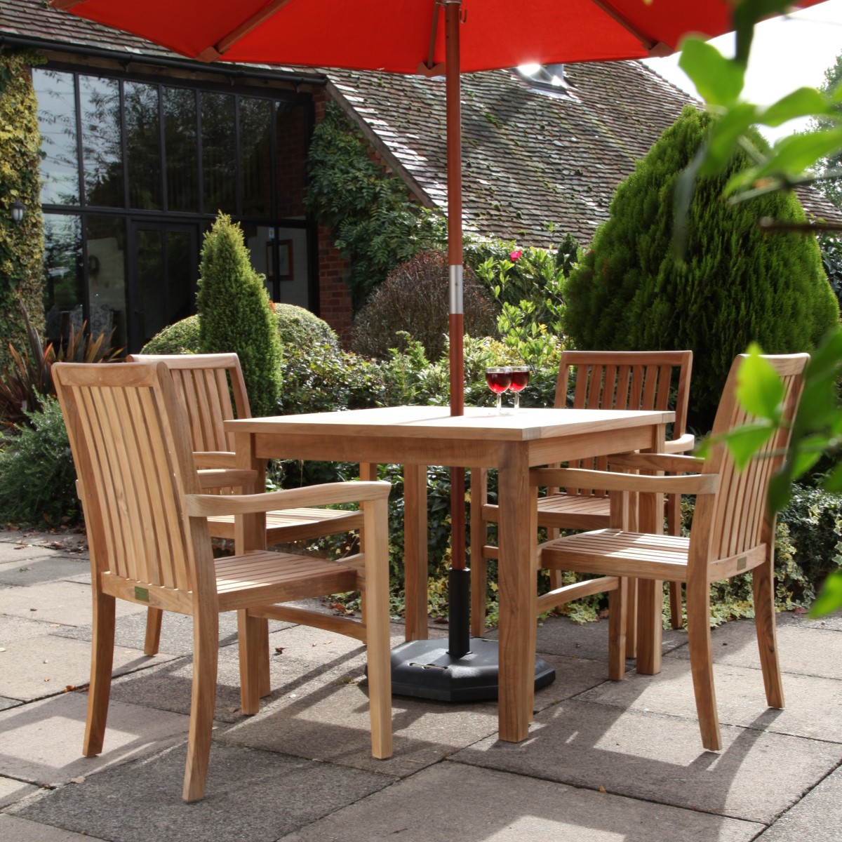 A teak outdoor square dining table and four armchairs on a patio with a red parasol