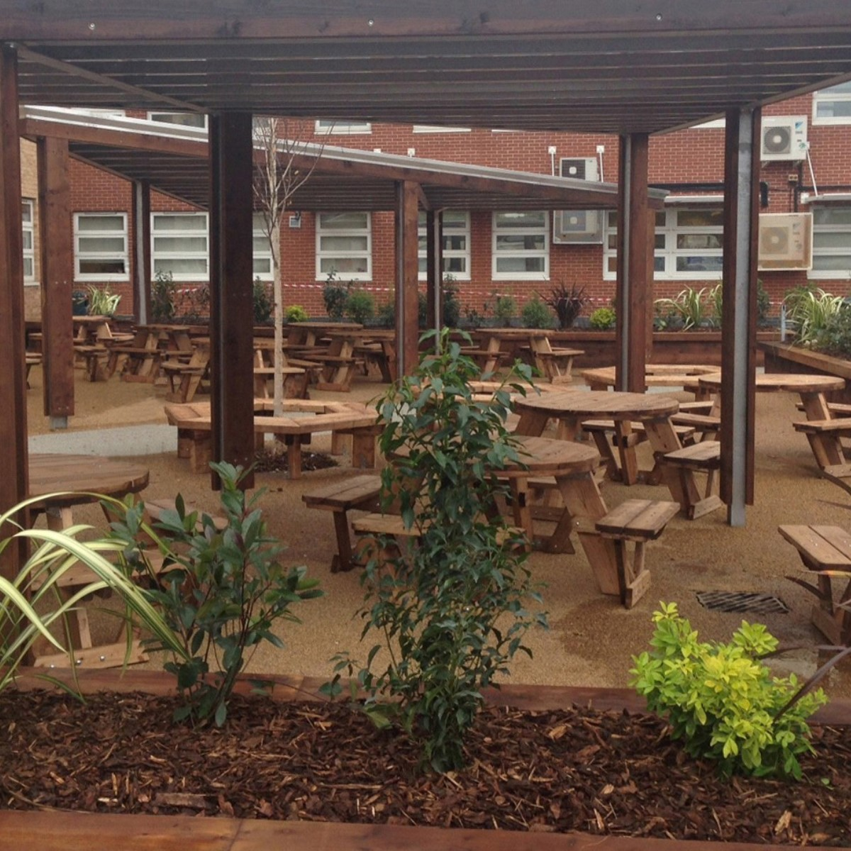 A pub patio with a metal shelter above round wooden picnic tables
