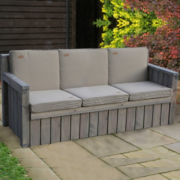 A wooden 3 seater outdoor sofa with grey cushions on a patio