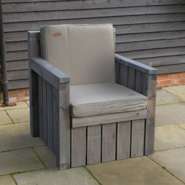 A wooden outdoor armchair with grey cushions on a patio