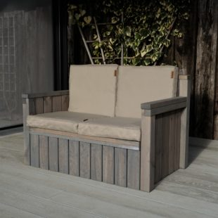 A chunky wooden outdoor 2 seater sofa with grey cushions on a deck