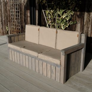 A 3 seater wooden outdoor sofa with grey cushions on a deck