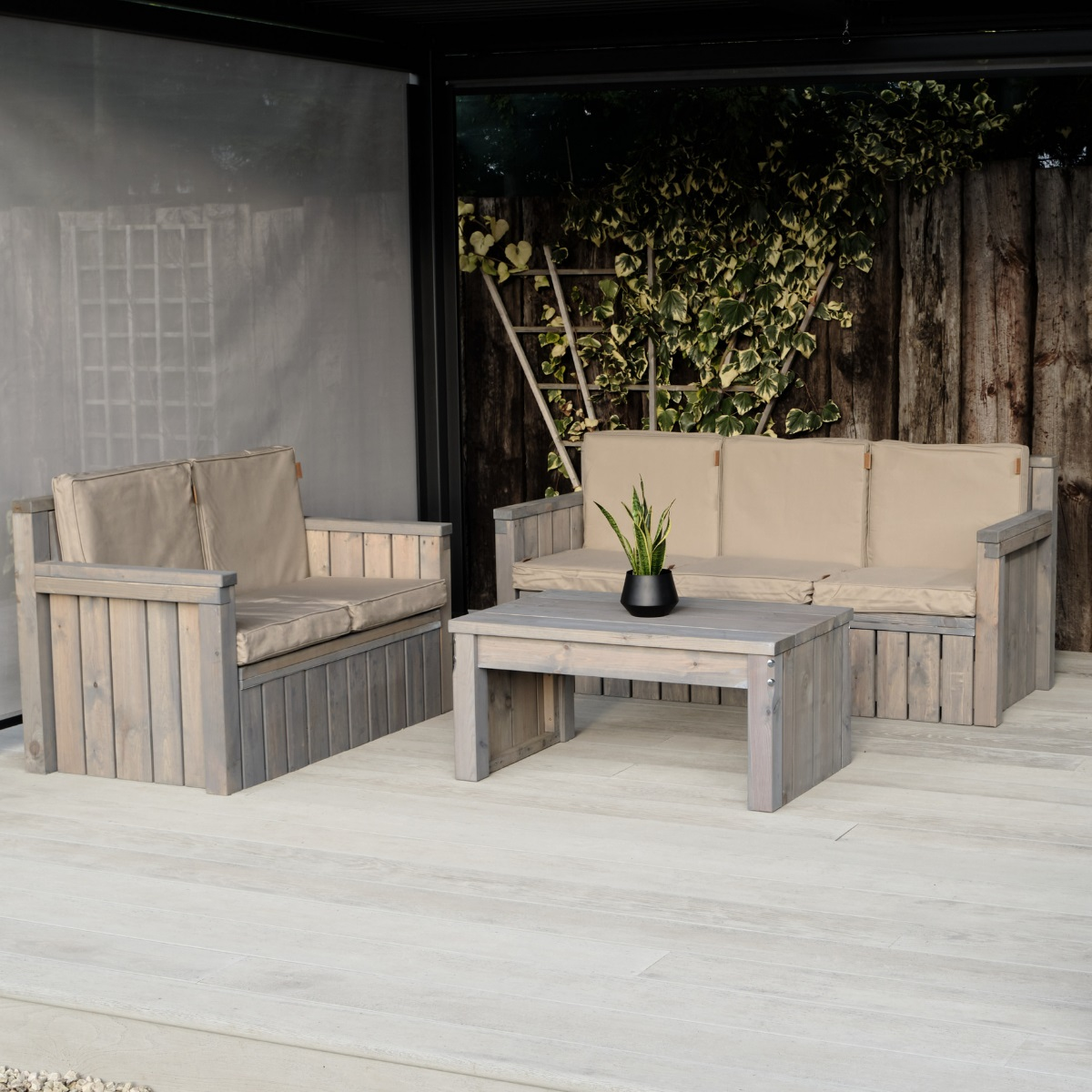 An outdoor wooden sofa set includes a 2 seater, 3 seater sofa and coffee table on a deck