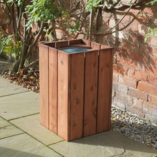 A square wooden litter bin with an open top on a patio
