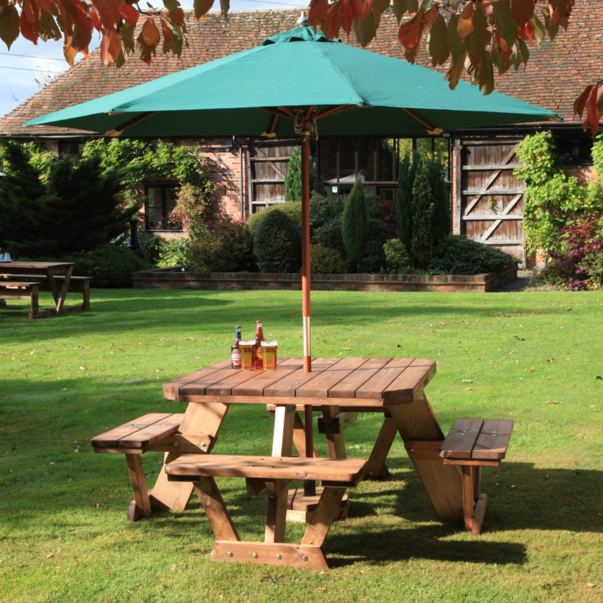 A square wooden 8 seater picnic table with a green parasol located on a lawn