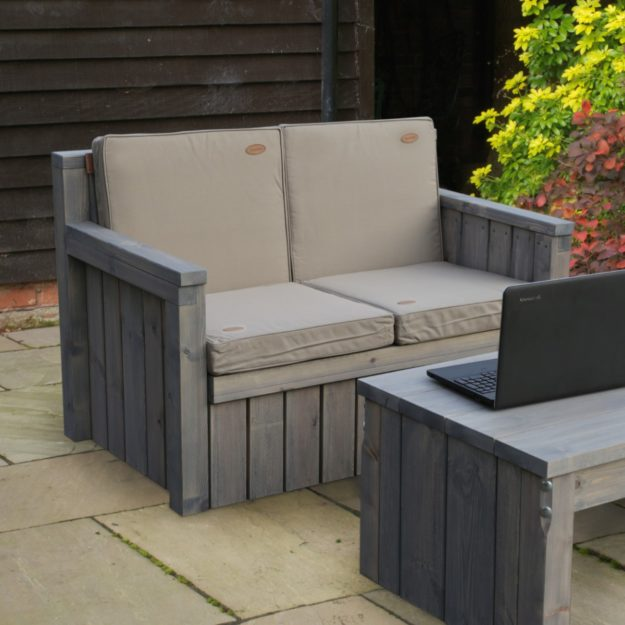 A 2 seater wooden outdoor sofa and matching coffee table on a patio