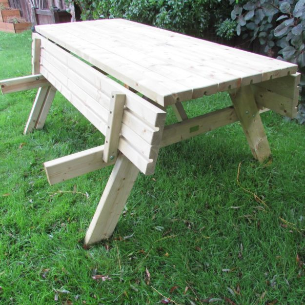 A wooden picnic table with foldable bench seats shown with bench seats folded up towards the table top