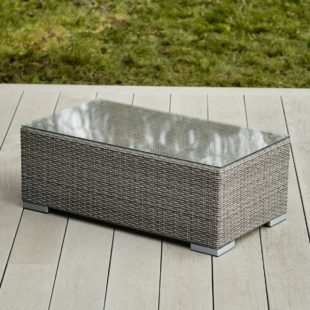 A grey rattan rectangular outdoor coffee table with a glass table top on a light grey garden deck