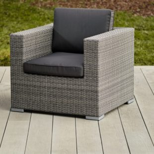 A cube shaped grey rattan outdoor armchair with dark grey cushions on a light grey deck