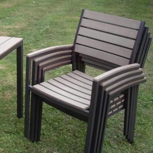 A light grey slatted plastic outdoor chair with a dark grey aluminium frame in a stack of 4 chairs on a lawn
