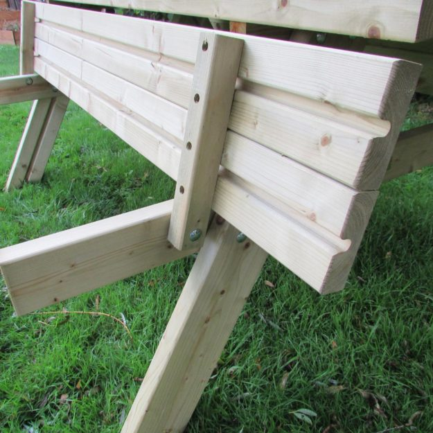 A close up of a wooden picnic table with the bench seat folded up towards the table showing the screws and hinge mechanism