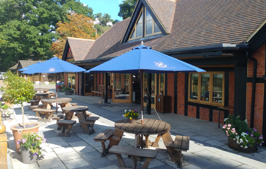 8 Seater Circular wooden picnic tables with blue parasols on the patio terrace at Bradfield College