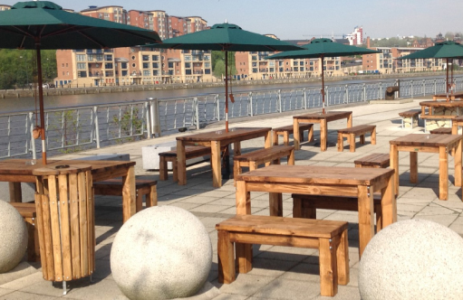 Six, strong, wooden rectangular tables and wooden benches located on the riverside patio of the Jury's Inn, Newcastle