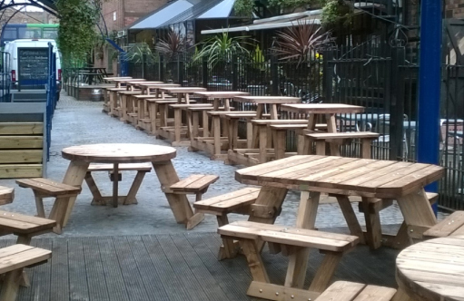 A range of wooden picnic benches in the courtyard of The Canal House Pub