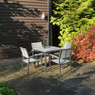 A square grey outdoor dining table with plastic slats and metal legs and four matching chairs on a patio