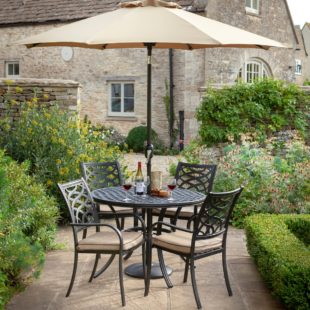 An attractive bronze cast aluminium lattice design round table and chairs set located on a patio