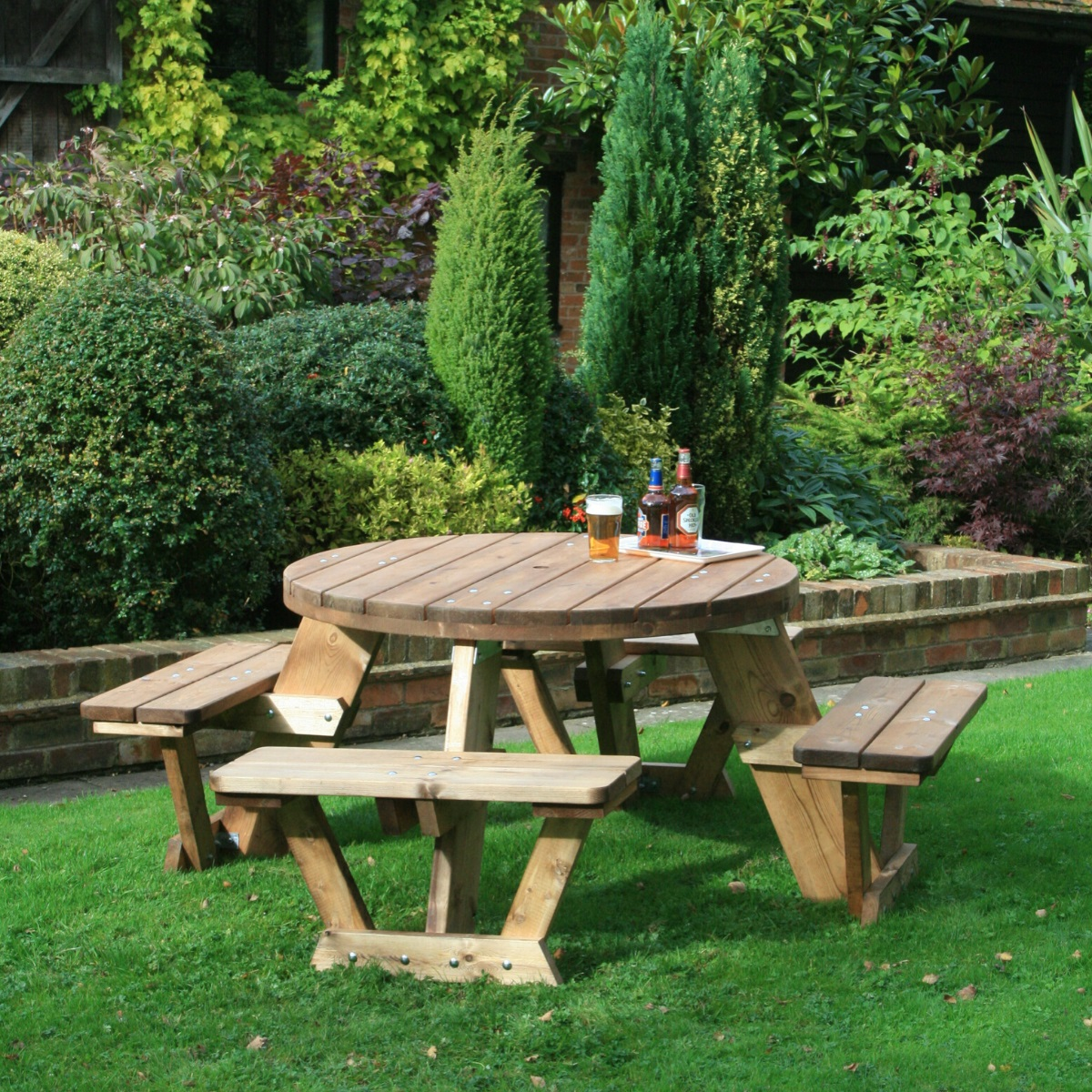 A circular wooden picnic table seating 8 people located on a lawn