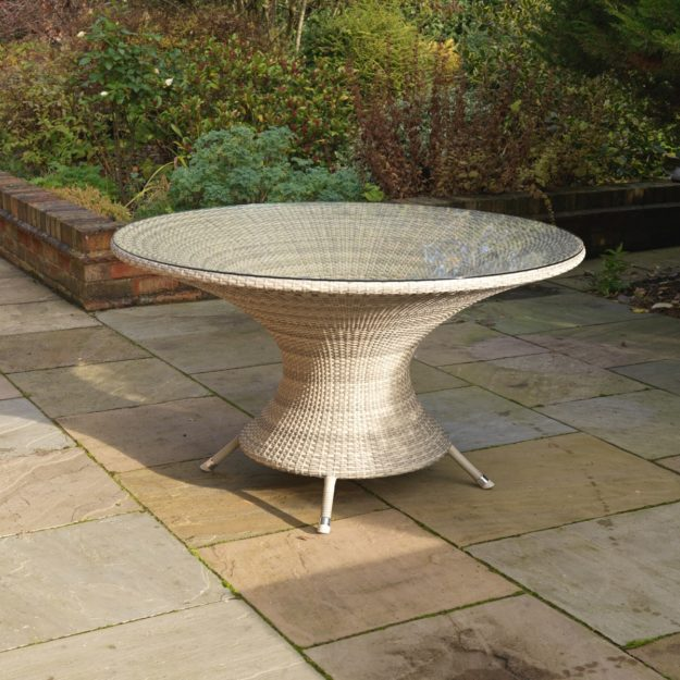 An elegant cream grey rattan weave round dining table with glass table top located on a patio