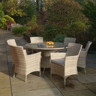 An elegant round dining table and arm chairs set in cream grey rattan located on a patio