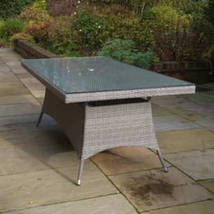 A Grey Rattan Rectangular Dining Table 2m long by 1m wide situated on a patio