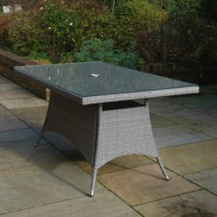A Grey Rattan weave rectangular outdoor dining table 1500mm long by 1000mm wide with glass table top situated on a patio