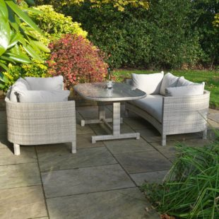 A luxury grey cream rattan sofa suite with large white cushions, comprises 2 3 seater sofas and a dining table
